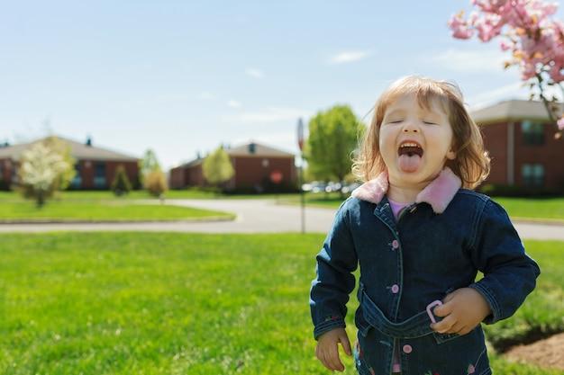 Hermosa chica jugando en la calle en la primavera