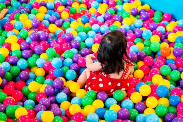 Hermosa chica jugando con pelotas de plástico.