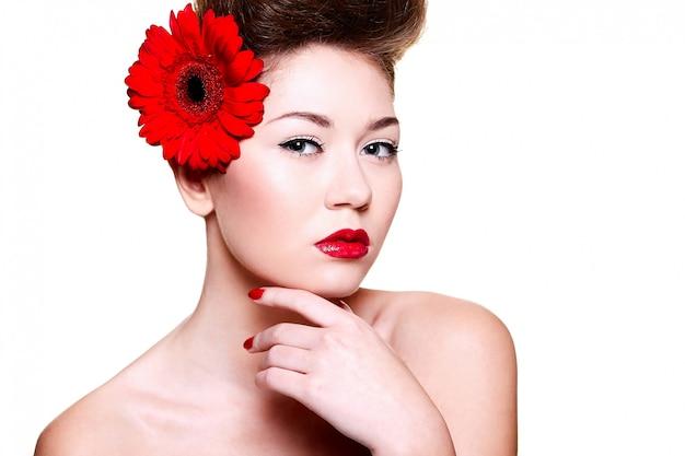 Hermosa chica con labios rojos y uñas con una flor en el pelo