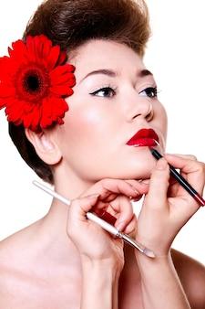 Hermosa chica con labios rojos y uñas haciendo su maquillaje