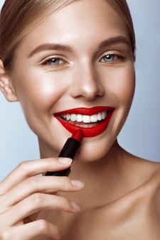 Hermosa chica con labios rojos y maquillaje clásico con lápiz labial en mano, cara de belleza