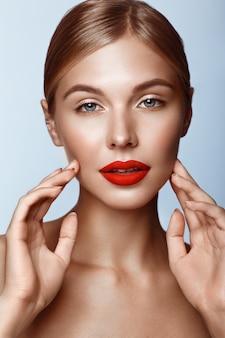 Hermosa chica con labios rojos y maquillaje clásico, rostro de belleza