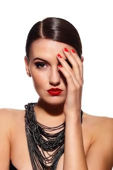 Hermosa chica con uñas y labios rojos