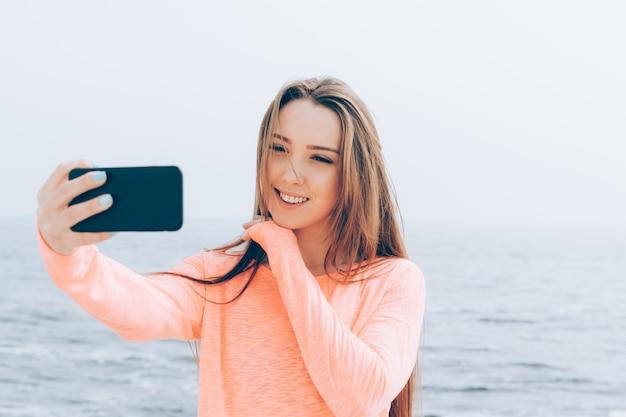Hermosa chica con largo cabello castaño toma fotos de ella misma en el teléfono en la playa
