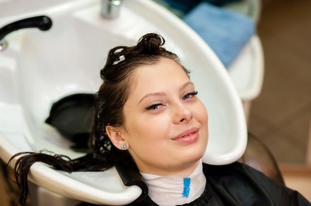 Hermosa chica lavarse el cabello en el salón