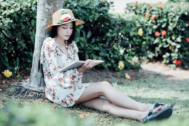 Hermosa chica leyendo un libro en el parque en la luz del sol de verano
