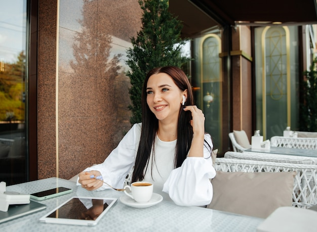 Una hermosa chica linda en un café bebe café en una mesa.