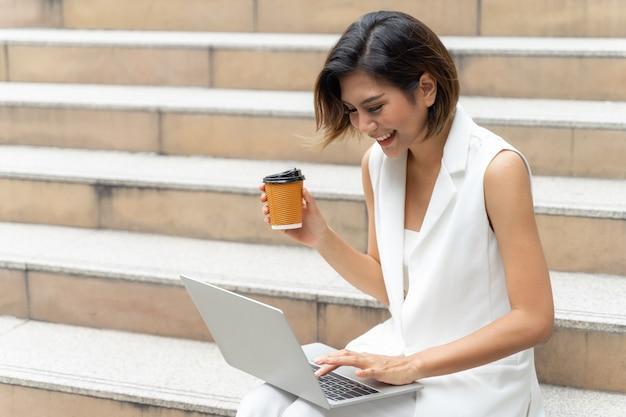 Hermosa chica linda sonriendo en ropa de mujer de negocios usando la computadora portátil en la ciudad urbana