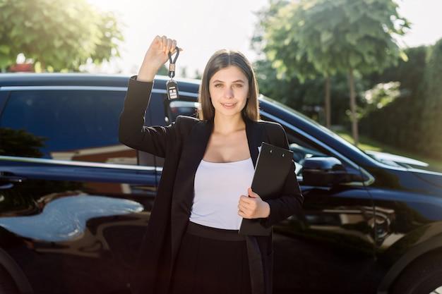 Hermosa chica con la llave del coche en la mano. vendedor de coches de mujer caucásica sosteniendo las llaves del coche, de pie delante del nuevo coche negro al aire libre en la feria de vehículos. alquiler de automóviles o concepto de ventas.
