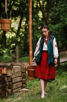 Hermosa chica lleva un cubo de agua con un vestido étnico tradicional