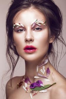 Hermosa chica con maquillaje artístico y flores.