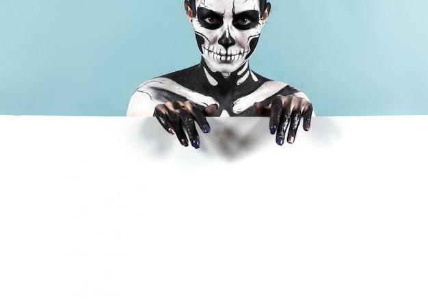 Hermosa chica con maquillaje esqueleto sobre el espacio de copia
