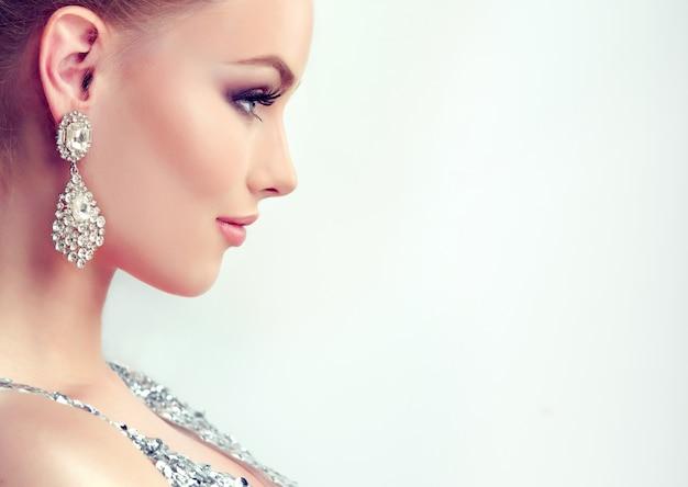 Hermosa chica con maquillaje de noche y grandes aretes de joyería
