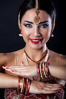 Hermosa chica con maquillaje oriental y joyería india, look de moda