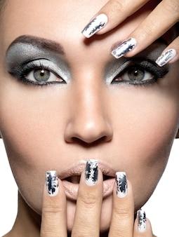 Hermosa chica con maquillaje plateado y clavos metálicos.