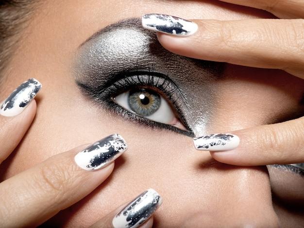 Hermosa chica con el maquillaje plateado de ojos y uñas metálicas.