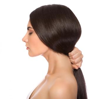 La hermosa chica con maquillaje en el salón de spa después de los procedimientos cosméticos mantiene el cabello