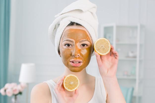 Hermosa chica con máscara facial marrón sosteniendo una rodaja de limón cerca de su rostro y sonriendo. foto de una niña recibiendo tratamientos de spa. concepto de belleza y cuidado de la piel