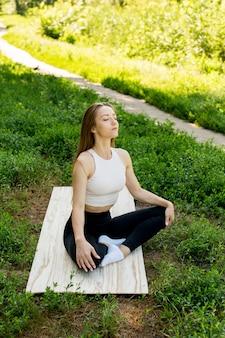 Hermosa chica medita en la naturaleza