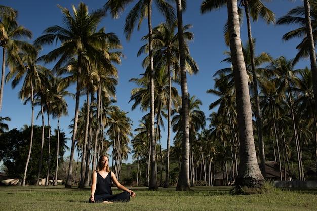 Hermosa chica medita en la naturaleza.