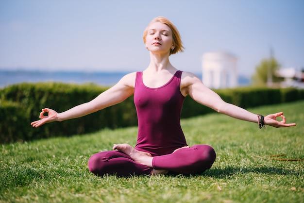 Hermosa chica medita en posición de loto sentado en el césped en un día soleado