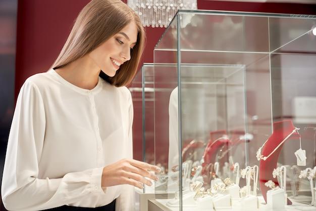 Hermosa chica mirando la vitrina con joyas de lujo