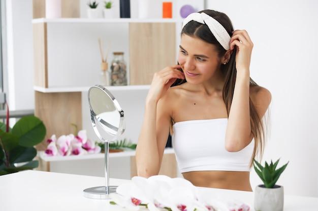 Hermosa chica mirándose en el espejo, cuidando su piel.