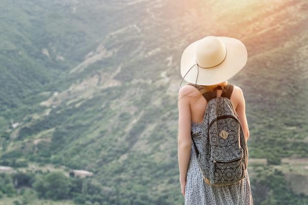 Hermosa chica con una mochila y un sombrero de pie contra una de montañas verdes