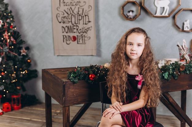 Hermosa chica de moda en vestido en casa cerca de la víspera de año nuevo y decoraciones de navidad y luces de colores
