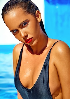 Hermosa chica modelo con cabello oscuro en traje de baño negro