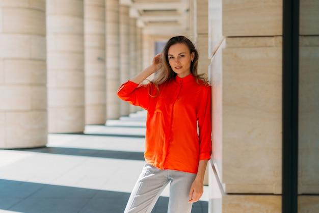 Hermosa chica modelo de pleno crecimiento posando en la cámara a la sombra del edificio
