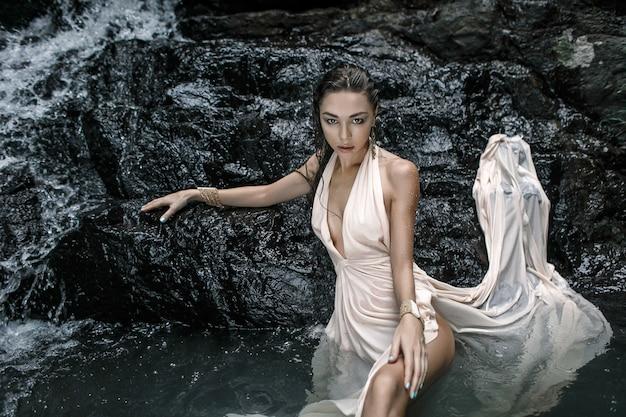 Una hermosa chica mojada con un vestido largo de moda en una cascada