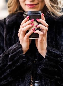 Una hermosa chica morena con un abrigo de piel negro sostiene un vaso con una bebida caliente en sus manos y sonríe. foto