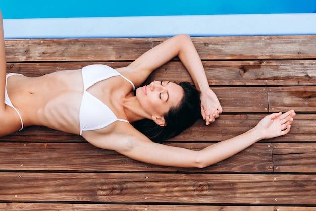Hermosa chica morena en buena forma y piel perfecta bronceada en una suite blanca de natación acostada cerca de la piscina manteniendo los ojos abiertos con una sonrisa suave