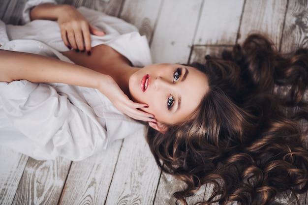 Hermosa chica morena con cabello ondulado acostado en el piso de madera