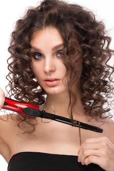 Hermosa chica morena con un cabello perfectamente rizado con rizado y maquillaje clásico. cara de belleza