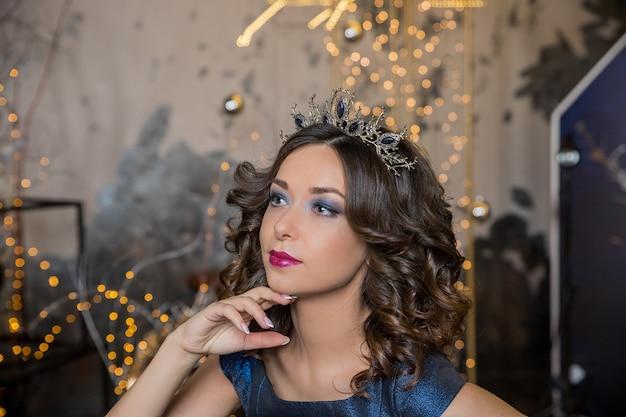 Hermosa chica morena con una corona de oro, aretes y maquillaje de noche profesional.