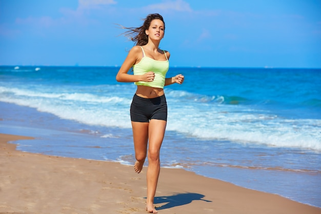 Hermosa chica morena corriendo en una playa de verano