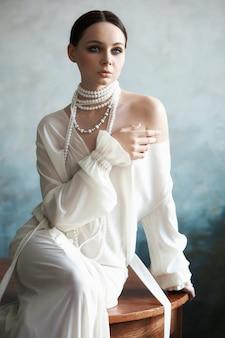 Hermosa chica morena delgada sentada en el sofá con un vestido blanco largo. retrato de una mujer con una joyería en el cuello. perfecto peinado y cosmética de la mujer, nueva colección de vestidos ligeros.