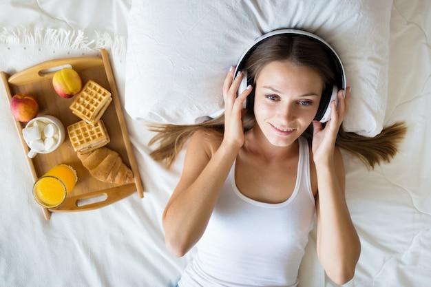 Hermosa chica morena escuchando música con auriculares en la cama