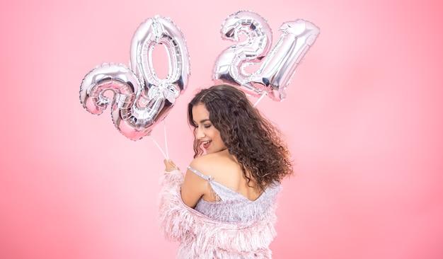 Hermosa chica morena con hombros desnudos en ropa de fiesta posando sobre un fondo rosa con globos para el nuevo año en sus manos