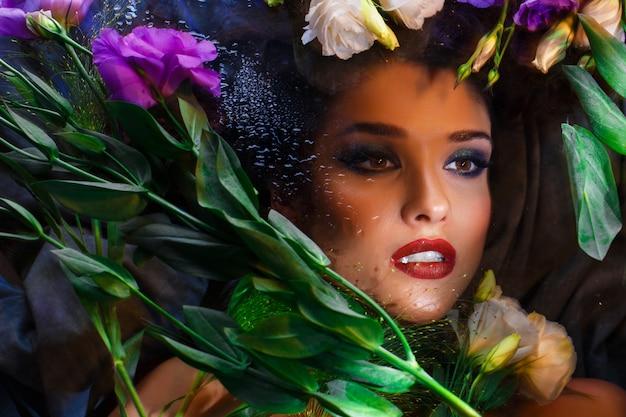 Hermosa chica morena con maquillaje brillante acostado entre eustomas.