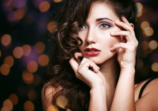 Hermosa chica morena. maquillaje saludable para cabello largo y festivo.