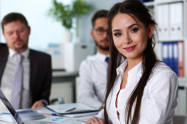 Hermosa chica morena secretaria sonriente en el lugar de trabajo