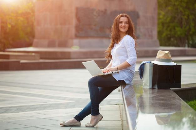 Hermosa chica morena está sentada en la calle con un portátil y compras.