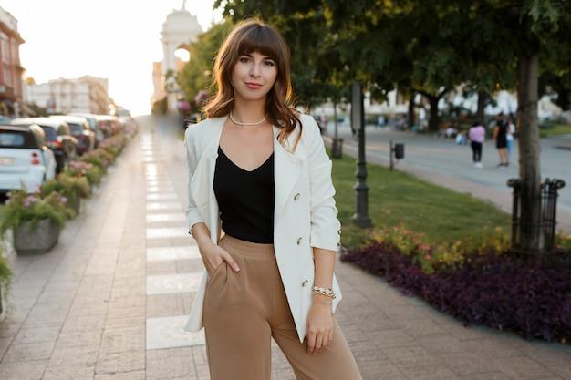 Hermosa chica morena sexy en ropa casual con figura perfecta caminando por el centro de la ciudad. estilo elegante. chaqueta blanca.
