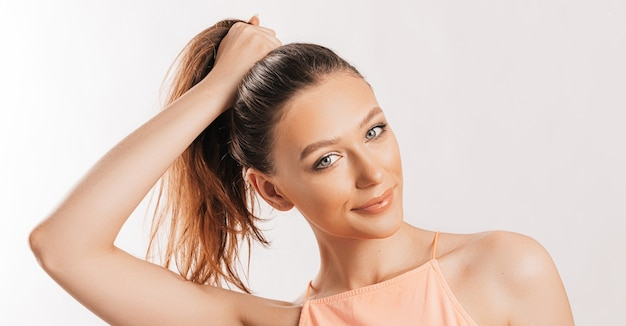 Una hermosa chica morena sostiene su cabello y hace su propio peinado. modelo joven con pelo largo, top naranja de moda sobre un fondo gris. la mujer sonríe y mira a la cámara.