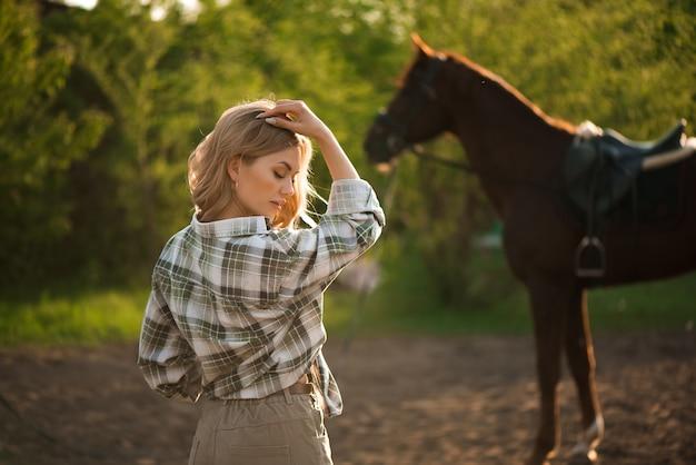 Hermosa chica morena con su caballo al aire libre