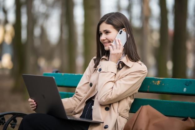 Hermosa chica morena tiene una llamada telefónica afuera en el parque de otoño