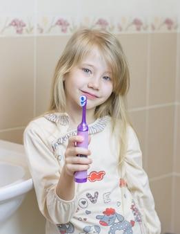 Hermosa chica muestra un cepillo de dientes eléctrico en el baño.